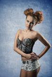 Voluptuous woman with pigtail hair-style. Glamour  redhead girl with pigtail hair-style posing with voluptuous body and wearing trendy corset adorned by shiny Royalty Free Stock Image