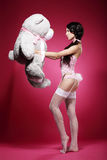 Voluptuous Woman in Tights and Garters with Big Soft Toy Stock Photos