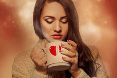 Voluptuous young brunette with hot drink in cup Royalty Free Stock Photos