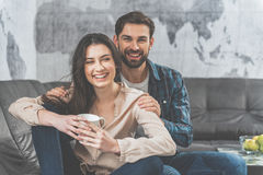 Voluptuous young couple having rest together. Joyful girl is drinking coffee and relaxing. Man is sitting behind her and embracing her with love. They are Royalty Free Stock Image
