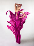 Voluptuous young woman with creative pink dress in. Studio on grey background Royalty Free Stock Photography
