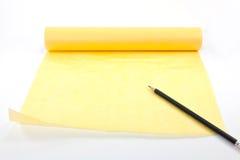 Voluta de papel amarilla con el lápiz negro Fotografía de archivo libre de regalías