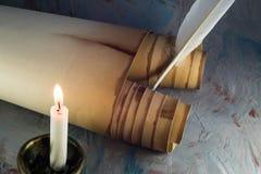 Voluta de papel vieja, canilla y vela ardiendo fotografía de archivo libre de regalías