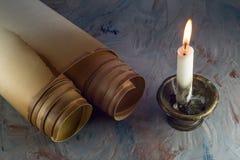 Voluta de papel vieja y una vela ardiente en una palmatoria vieja imagenes de archivo