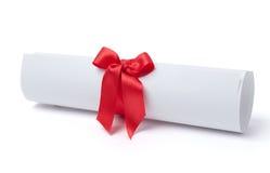 Voluta del diploma de la graduación atada con la cinta roja Foto de archivo libre de regalías