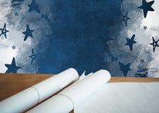 Volutas de los planes de papel en el escritorio con la pizarra y las estrellas Fotos de archivo libres de regalías