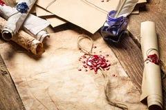 Volutas viejas, cera de lacre y tinta azul en la tabla de madera Foto de archivo
