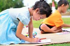 Volviendo a la escuela, niños que dibujan y que pintan sobre g verde Imagen de archivo libre de regalías