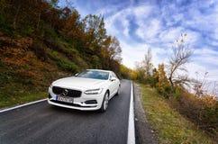 Volvo blanco S90 que conduce en naturaleza foto de archivo