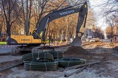 The Volvo excavator. ODESSA, UKRAINE - march 31, 2017: The Volvo excavator carries out reconstruction of Preobrazhenskaya Street stock photo