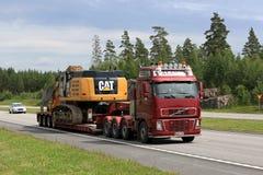 Volvo FH Hauls Cat 349E Tracked Excavator Stock Image