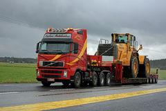 Volvo FH12 Hauls Wheel Loader on Rainy Day Stock Image