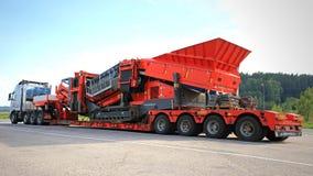 Volvo FH schleppt eine schwere Last auf doppeltem Tropfen-Plattform-Anhänger Lizenzfreies Stockfoto