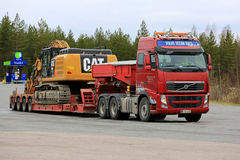 Volvo FH Semi Hauls Cat Excavator on Flat Trailer Royalty Free Stock Photography