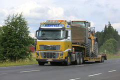 Volvo FH16 Semi Hauls Wheel Loader Through Rural Scenery Royalty Free Stock Photography