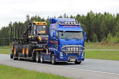 Volvo FH Transports Ponsse Forwarder along Road royalty free stock image
