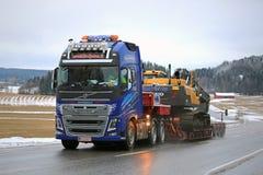 Volvo FH16 600 Truck Heavy Haul along Highway. SALO, FINLAND - FEBRUARY 14, 2016: Volvo FH16 600 truck hauls Volvo EC300DLR Crawler excavator on lowboy trailer royalty free stock image