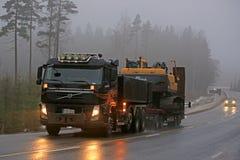 Volvo FM Semi Hauls Crawler Excavator in Fog Stock Photos