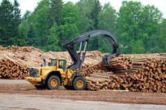 Volvo L180F HL Log Loader Lifting Logs. KYRO, FINLAND - JUNE 7, 2014: Volvo L180F High Lift wheel loader working at mill lumber yard.  The L180F HL features a 3 Royalty Free Stock Images