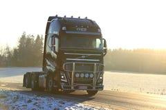 Volvo negro FH semi que acarrea en la puesta del sol de oro Fotos de archivo