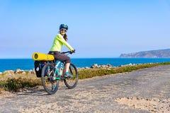 Volwassen aantrekkelijke vrouwelijke fietser die haar bergfiets berijden door de oceaankust en terug de camera bekijken stock afbeelding