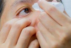 Volwassen Aziatische vrouw die oogdalingen in haar bruine ogen toepassen Oogzorg stock foto's