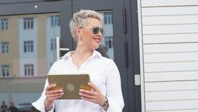 Volwassen Bedrijfsvrouw met tabletpc met bureaudistrict op achtergrond stock videobeelden