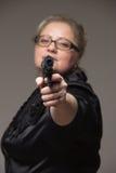 Volwassen bedrijfsvrouw met zwart kanon op een grijze achtergrond Royalty-vrije Stock Afbeelding