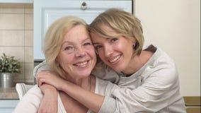 Volwassen dochter die haar bejaarde moeder koesteren stock footage