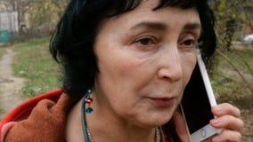 Volwassen elegante donkerbruine vrouw die emotioneel op haar smartphone spreken stock videobeelden