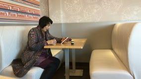 Volwassen elegante vrouw in glazen, die op een comfortabele bank zitten stock video