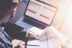 Volwassen elegante zakenman in oogglazen die op zonnig kantoor aan laptop werken terwijl het zitten bij houten lijst De medewerke royalty-vrije stock fotografie