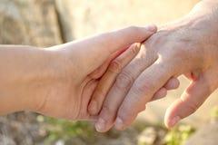 Volwassen en jonge vrouwen die handen houden stock foto