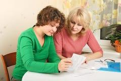 Volwassen en jonge vrouwen met documenten stock foto's