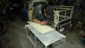 Volwassen gebaarde mens in GLB-het schilderen met borstel op de autodelen in garage stock footage