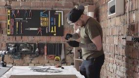 Volwassen gebaarde mens het schroeven details die zich bij de lijst in garage bevinden Het mensenwerk in een workshop De raad met stock videobeelden