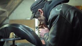 Volwassen gebaarde mens in het zwarte GLB en jasje schilderen met luchtpenseel op de motorfietsvleugel in douanegarage stock video