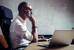 Volwassen gebaarde zakenman die wit overhemd dragen en bij de houten lijst in moderne zolder werken Mens het maken neemt nota van Stock Afbeelding