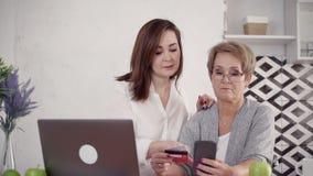 Volwassen gerijpte vrouw twee bij huis dat kaart gebruikt en cellulair voor sho stock videobeelden