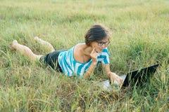 Volwassen glimlachende vrouw met glazen die computerlaptop op gras met behulp van Wijfje blogger, freelancer werkend in aard stock afbeeldingen