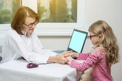 Volwassen glimlachende vrouwelijke arts en haar weinig patiënt Het kind en de arts houden handen royalty-vrije stock foto