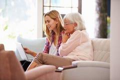 Volwassen Kleindochter die Grootmoeder met Computer helpen stock foto