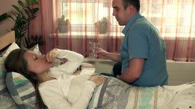 Volwassen man die voor zieke vrouw geven de verpleger geeft pil aan zieke patiënt stock video