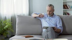 Volwassen mannelijke zitting op bank en lezingsnieuws op tablet, moderne technologieën stock afbeelding
