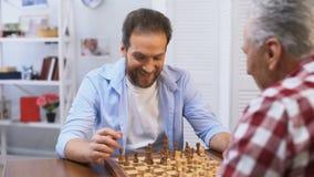 Volwassen mannetjes die schaak, vader en zoons het concurreren, hobby en vrije tijdsactiviteit spelen stock footage