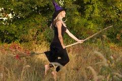 Volwassen meisje in de vliegen van het heksenkostuum op bezemsteel Stock Foto