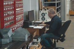 Volwassen mens die bij de computer bij fabriek van productiecnc machine met draaibanken werken royalty-vrije stock afbeeldingen