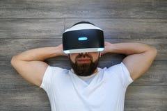 Volwassen Mens die op zijn rug in virtuele glazen op een houten vloer liggen stock afbeeldingen