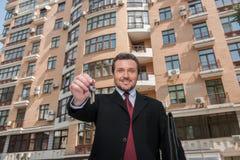 Volwassen mens die sleutel houden aan droomhuis met het voortbouwen op achtergrond Royalty-vrije Stock Fotografie
