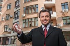 Volwassen mens die sleutel houden die aan droomhuis bij de bouw van achtergrond wordt geïsoleerd Stock Foto's